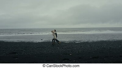 Copter flying near the young couple in icelandic sweater. Man and woman walking, holding hands on black volcanic beach.