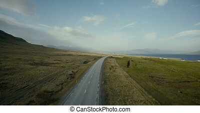 Copter flying over the traffic road with cars riding on it. Beautiful scenic view of the fields and shore of the ocean.