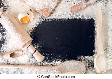 Copy space around utensils, flour and egg on black background. Top view. Frame. Ingredients and tools for baking.