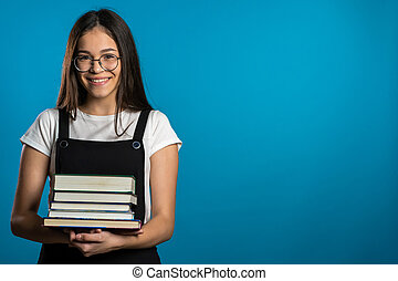 Copy space. Asian student girl on blue background in the studio holds stack of university books from library. Woman smiles, she is happy to graduate.