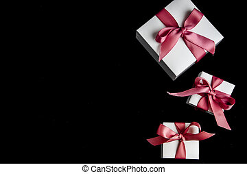 copy space for text gift boxes with pink ribbon on black background