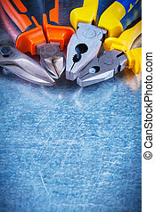 Copy space image of tin snips gripping tongs nippers on scratched vintage metallic background construction concept.