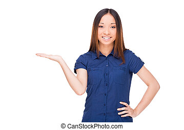 Copy space in her hand. Cheerful young Asian woman holding a copy space and smiling while standing isolated on white
