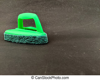 Copy space of green color bathroom scrubber brush with handle isolated on black background.