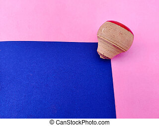 Copy space of small wooden spinning top isolated on blue and pink background