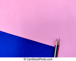 Copy space of two sharp pencils in black and red color isolated on pink and blue background