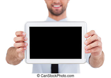 Copy space on digital tablet. Cropped image of cheerful young man in formalwear showing his digital tablet and smiling while standing isolated on white background