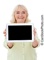 Copy space on her digital tablet. Happy senior woman showing her digital tablet and smiling while standing isolated on white background