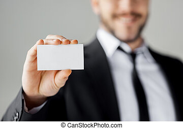 Copy space on his business card. Cheerful young man in formalwear showing his business card and smiling while standing against grey background