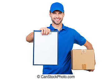 Copy space on his clipboard. Cheerful young courier stretching out clipboard and smiling while standing against white background