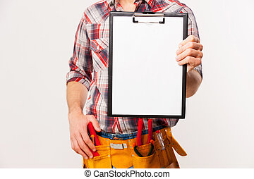 Copy space on his clipboard. Close-up of handyman with tool belt stretching out clipboard with paper standing against grey background