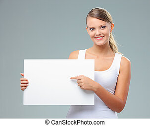 Portrait of a beautiful girl pointing at copy space