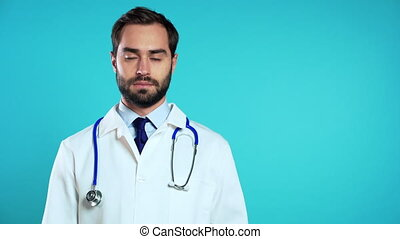 Copy space portrait of young handsome man in professional medical white coat is isolated on blue studio background. Doctor with beard and stethoscope