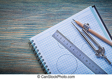 Copybook ruler pair of compasses pencil on vintage wooden board
