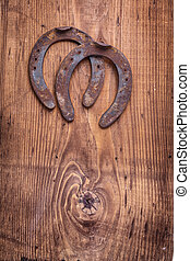 copyspace image two old cast iron metal western horse shoeing accessory horseshoes on antique wooden background happy concept vertical version
