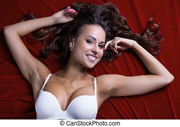 coqueto, busty, modelo, acostado, en, raso, bedsheet