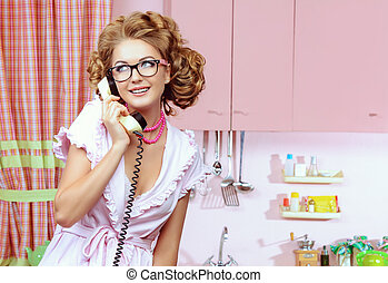 Beautiful sexy pin-up girl talking on the phone on a pink kitchen. Fashion.