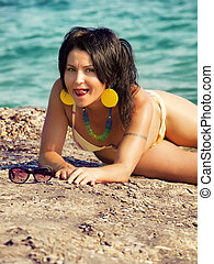 coquettish girl in bikini laying at sea rocks