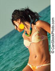 coquettish woman in bikini laying at sea rocks