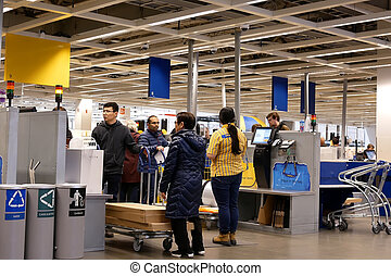 Motion of people paying product at self check out counter inside Ikea store in Coquitlam BC Canada