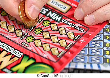 Coquitlam BC Canada - March 26, 2014 : Scratching lottery tickets. The British Columbia Lottery Corporation has provided government sanctioned lottery games in British Columbia since 1985.