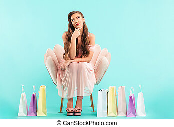 cor-de-rosa, azul, 20s, mulher, foto, coloridos, sacolas, sentando, pensando, poltrona, sobre, após, isolado, lotes, fundo, sonhar, shopping, vestido
