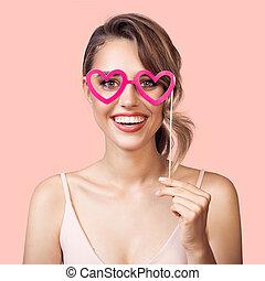 cor-de-rosa, coração, mulher, mão., alegre, experiência., papel, segurando, retrato, partido, sorrindo, óculos
