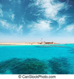 Coral reef and island. Blue cloudy sky and ocean