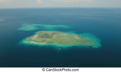 Aerial view coral reef, atoll with turquoise water in the sea. Tropical atoll, coral reef in ocean waters. 4K video. Travel concept. Aerial footage.