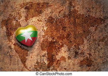 corazón, con, bandera nacional, de, myanmar, en, un, vendimia, mapa del mundo, grieta, papel, fondo.