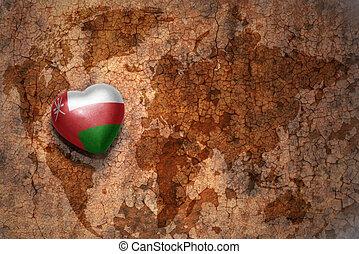 corazón, con, bandera nacional, de, omán, en, un, vendimia, mapa del mundo, grieta, papel, fondo.