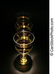 Cordials - Three cordials in a row with gold liquid, lit...