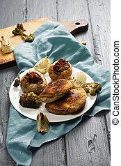 Cordon bleu cutlets and stuffed potatoes on a wooden ...