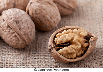Core of cracked nut close-up, group of brown Circassian walnuts on the sackcloth background