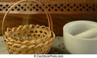 coriander seeds falling in a basket