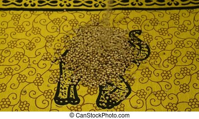 coriander seeds falling on an indian fabric