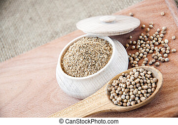 coriander seeds in a wooden spoon,