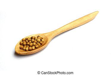 coriander seeds in wooden spoon