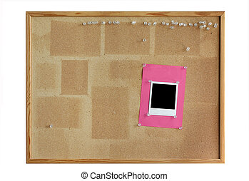 cork board with empty photo frame