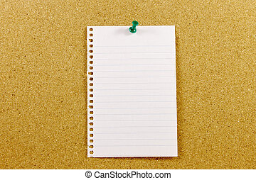Sheet of paper to write a message. Pinned on a cork bulletin board.