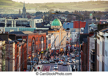 Cork, Ireland city center with various shops, bars and restaurants. Car traffic and people at the street. Mountains at the background
