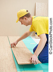 cork worker at flooring work - One carpenter worker laying ...