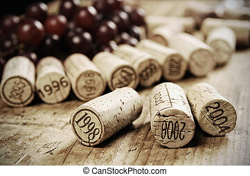 corks of different wine years in a row, red grapes in the...