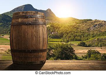 corkscrew and wooden barrel, vineyard on background