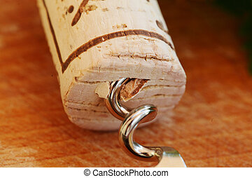 Corkscrew with wine cork, background