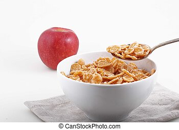 corn and rice flakes in white bowl and red Apple