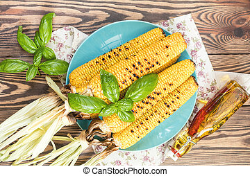 Corn baked in olive oil and salt on blue dish on dark...