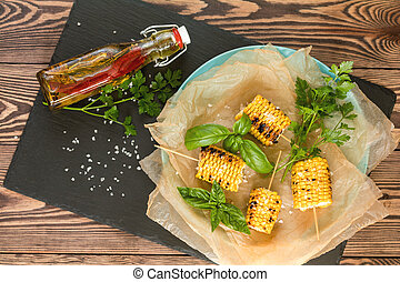 Corn baked in olive oil, with pepper, salt and basil on blue...