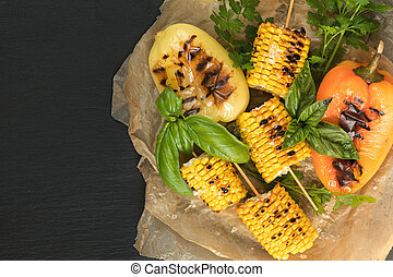 Corn baked in olive oil, with pepper, salt and basil on blue dish on a black stone surface. Vegetarian, vegan menu