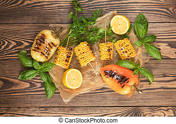 Corn baked in olive oil, with pepper, salt and basil on parchment paper on a dark surface